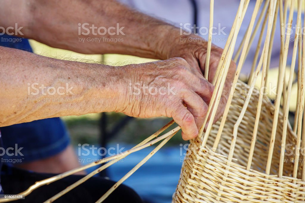 Man's hands making a wicker basket under sunny day stock photo