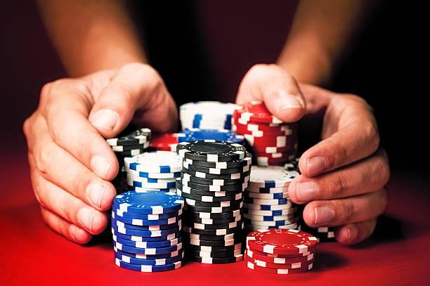 Homme mains déplacer les gains en jetons de casino sur la table rouge. - Photo