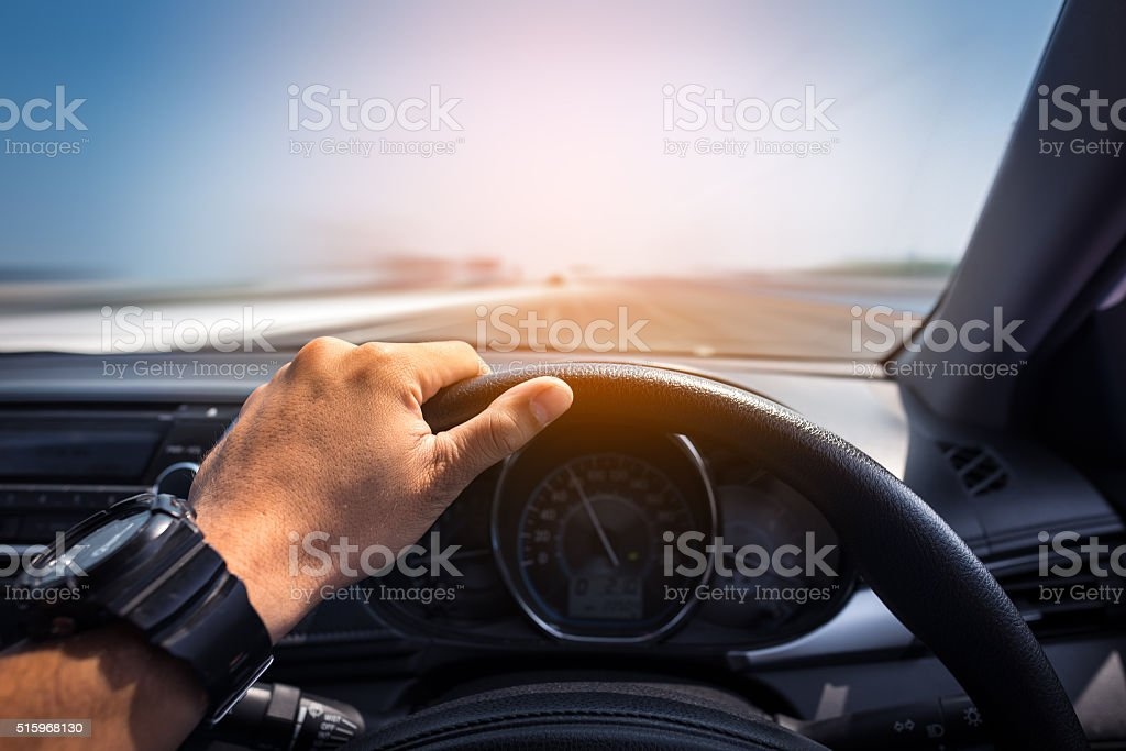 Man's hands of a driver with mobile phone stock photo