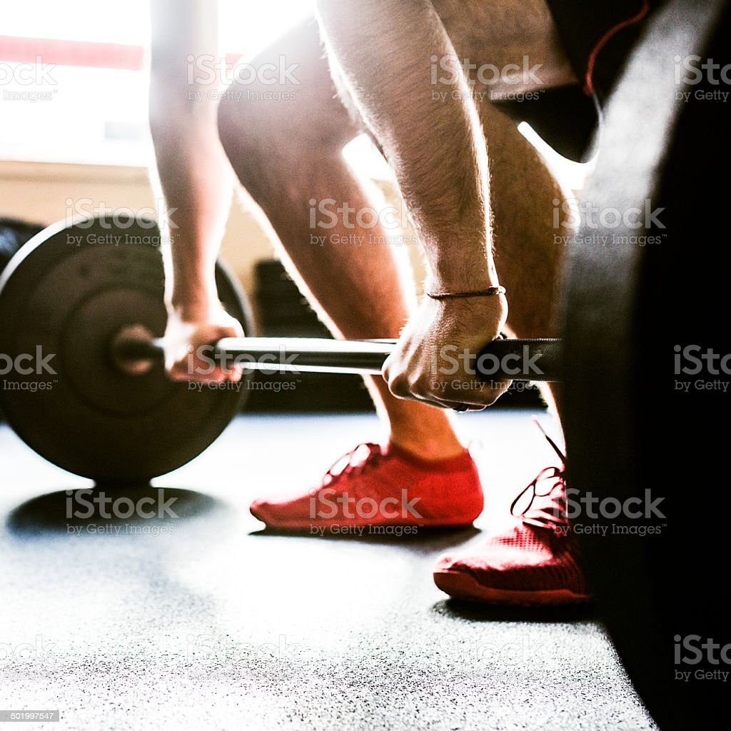 Mans Hands on Barbell Weights stock photo