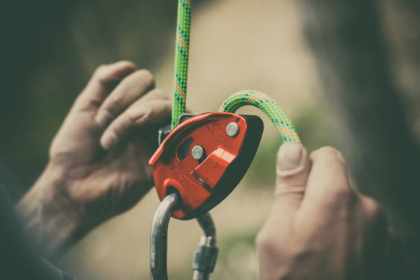 Man's hands operating a rock climbing belaying device stock photo
