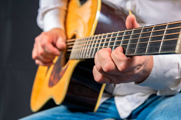 Man's hands playing acoustic guitar stock photo