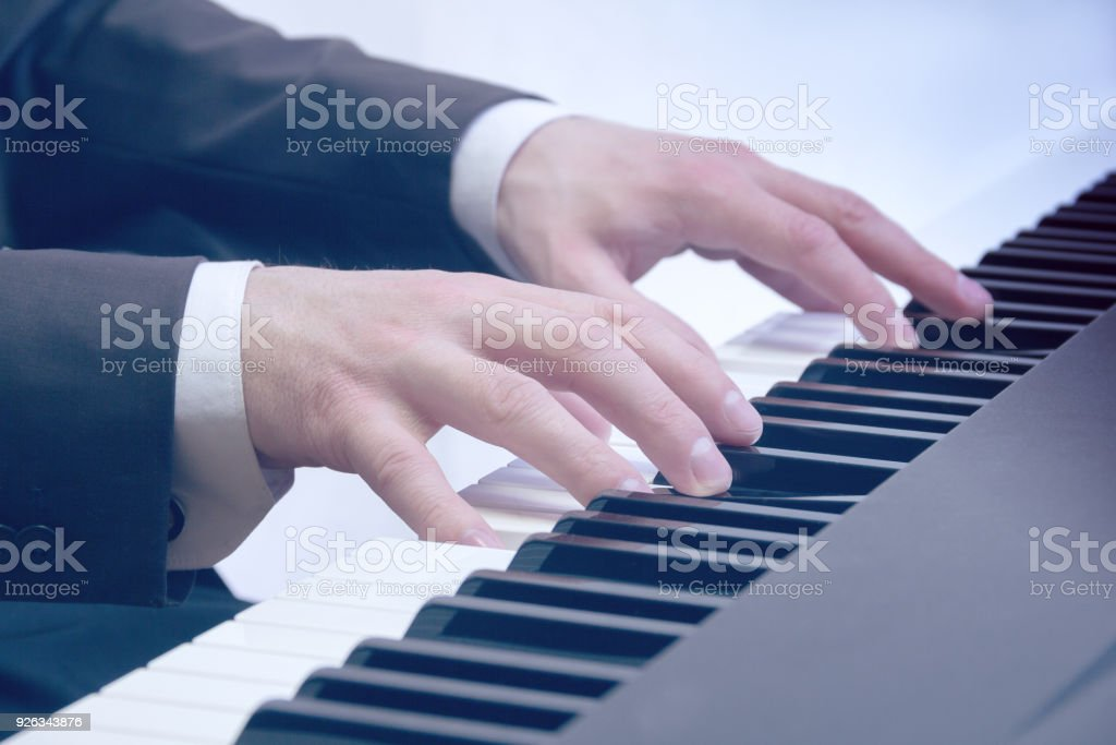 man's hands playing on a piano at the concert stock photo