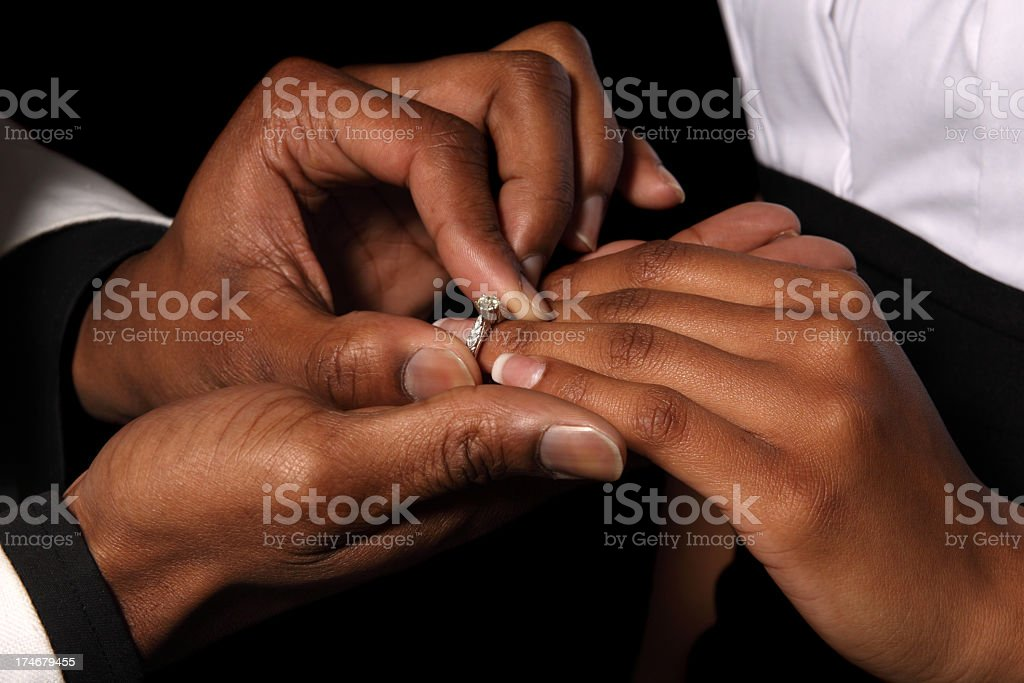 Mans hands putting an engagement ring on a woman's finger  stock photo