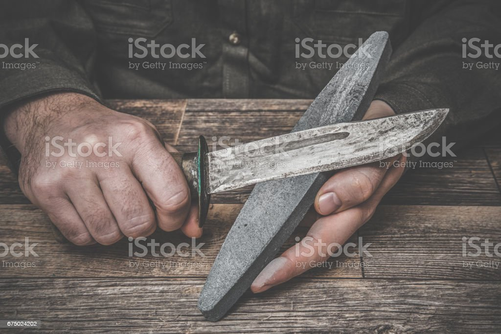Man's hands sharpening old knife on the wooden table. Dark, vintage atmosphere. stock photo