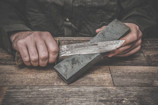 man's hands sharpening old knife on the wooden table. dark, vintage atmosphere. - table knife stock photos and pictures