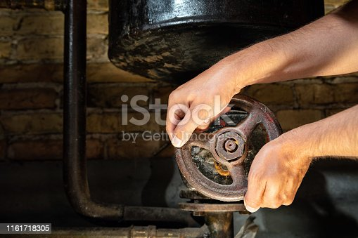 Mans hands trying to turn rusty valve on boiler room pipes. Old metal boiler generating heating and delivering it to home through pipeline