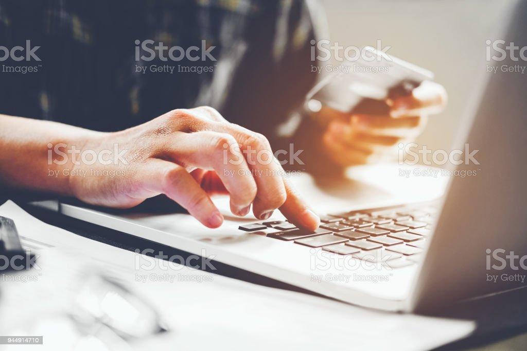 Die Hände des Mannes Laptop-Tastatur tippen und halten Sie Kreditkarten-online-shopping-Konzept – Foto
