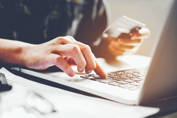 Man's hands typing laptop keyboard and holding credit card online shopping concept stock photo
