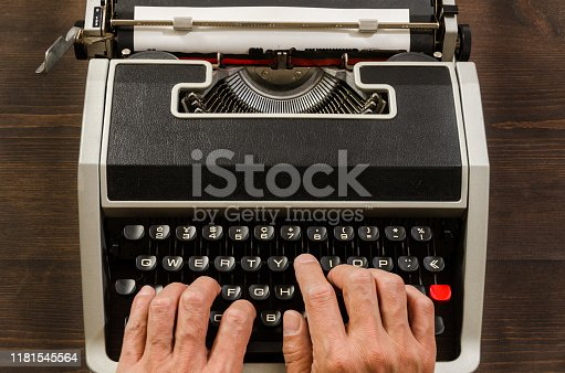 Man's hands typing with old typewriter on wooden desk.