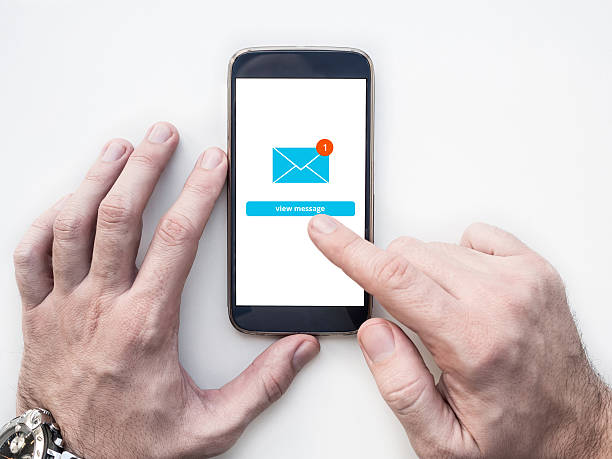 man's hands using smartphone with email app interface on screen - topics stock photos and pictures