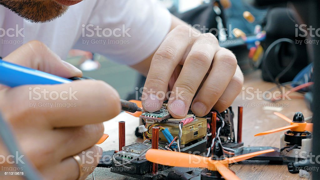 Man's hands welding details assembling FPV drone stock photo