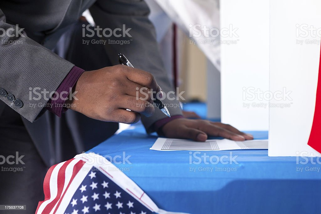 Man's hands while voting in election vote booth royalty-free stock photo