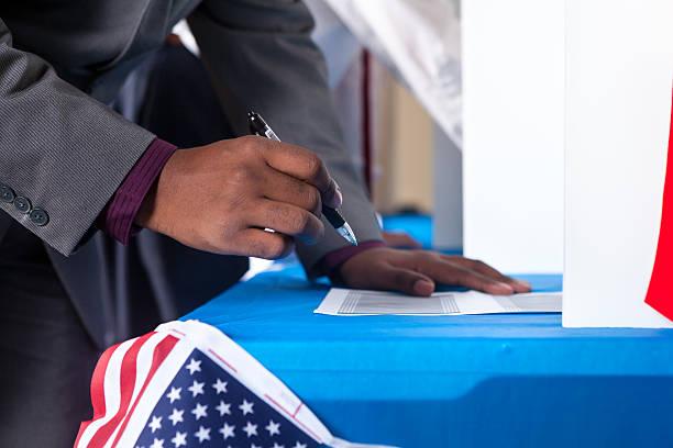 man's hands while voting in election vote booth - voting hands stockfoto's en -beelden