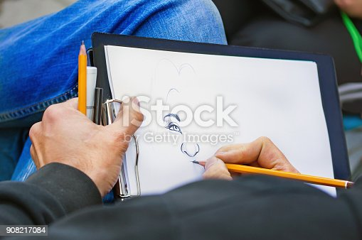 istock Man's hands with pencils drawing woman's portrait 908217084