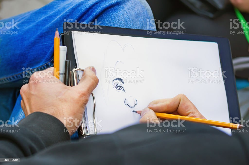 Man's hands with pencils drawing woman's portrait stock photo