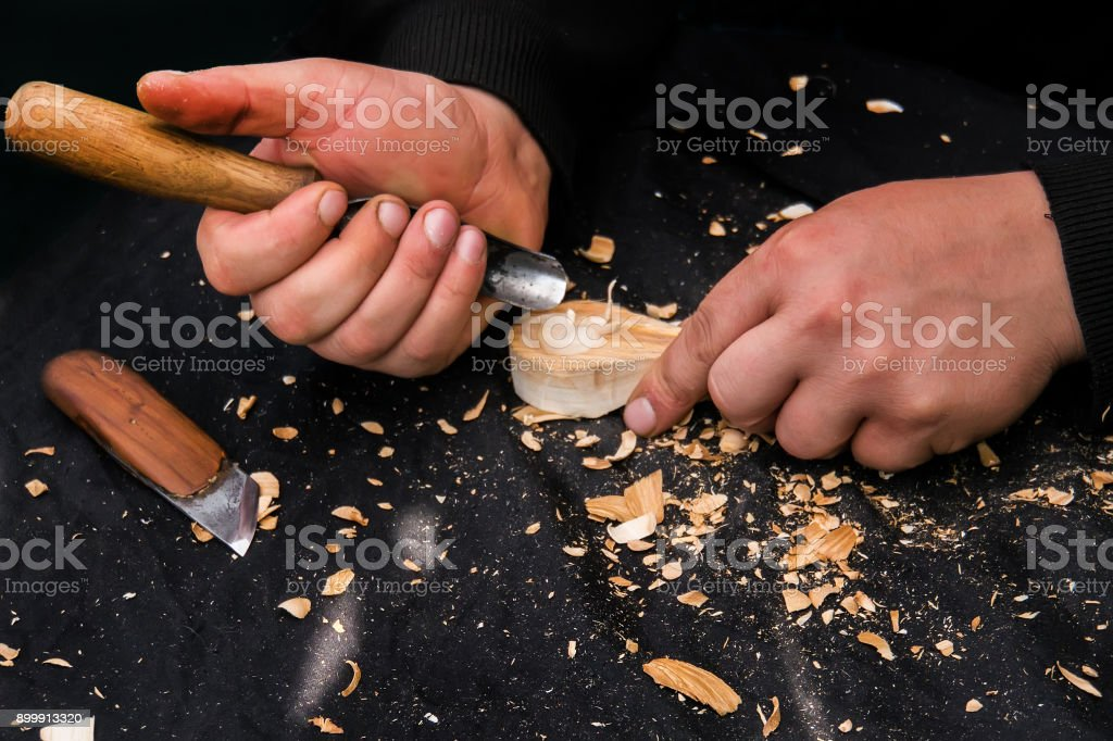 Man's hands working suit carving a wooden stock photo