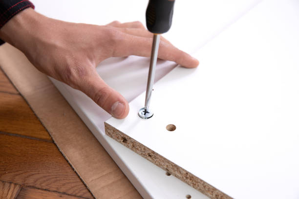 Man's hands working with a screwdrive. Installation of big bedroom wardrobe – zdjęcie