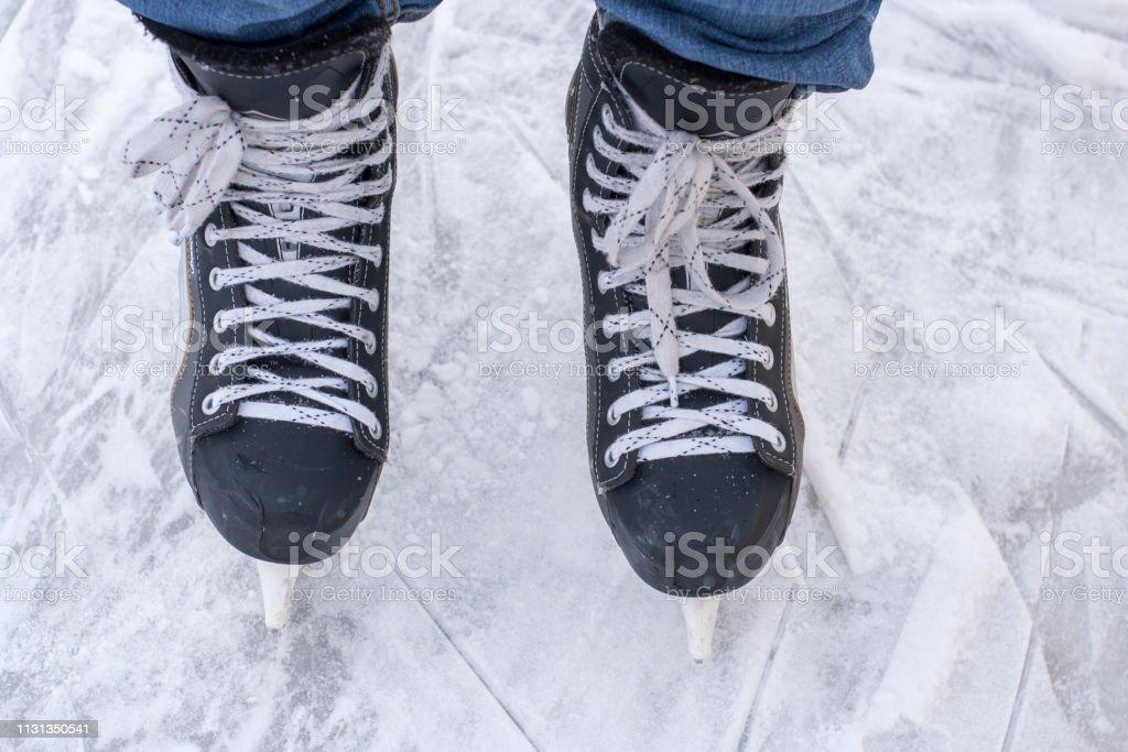 Man\'s hockey skates on ice background. People skate on the rink.