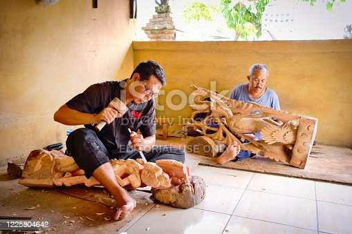 Bali, Indonesia - January, 2020: A mans is making wooden crafts in Bali Island, Indonesia