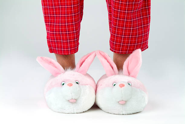 Man's legs in bunny slippers stock photo