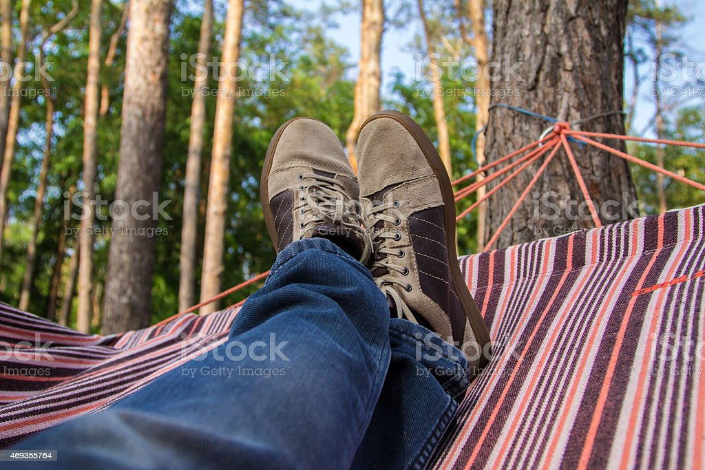 Man's legs in hammock on a forest background. POV stock photo