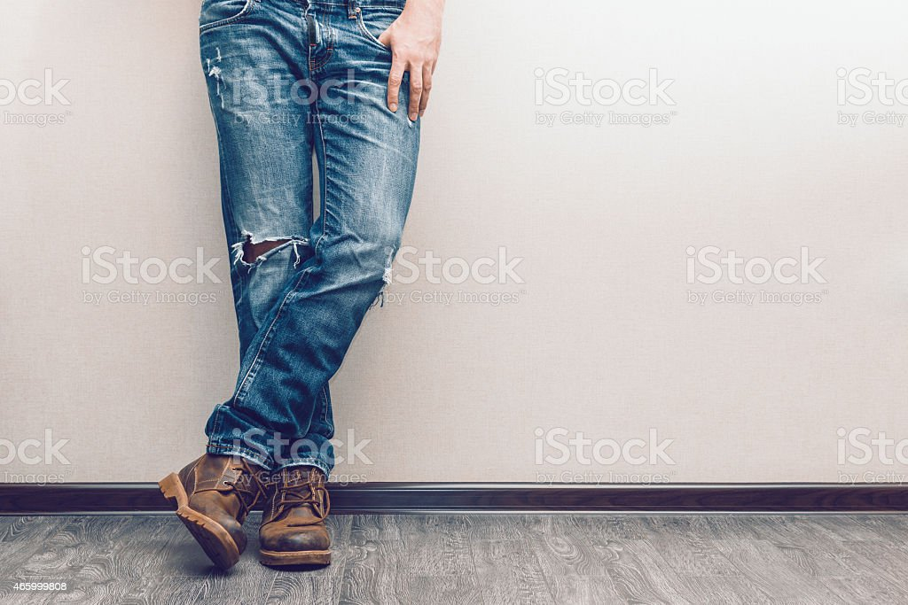 Mans legs in jeans and boots leaning on a white wall stock photo