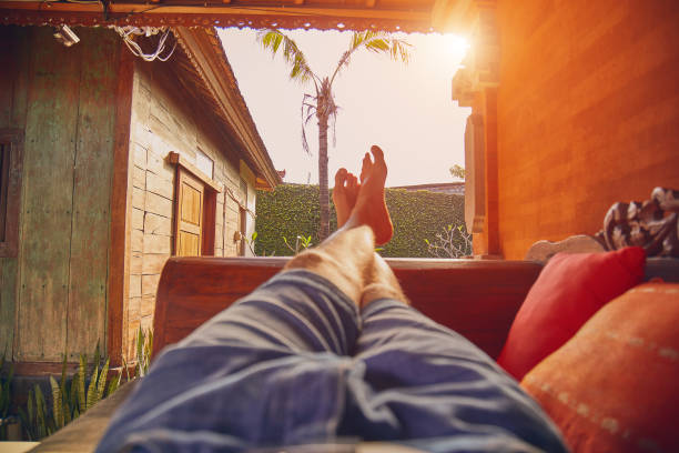Man's legs on a porch sofa in summertime. stock photo