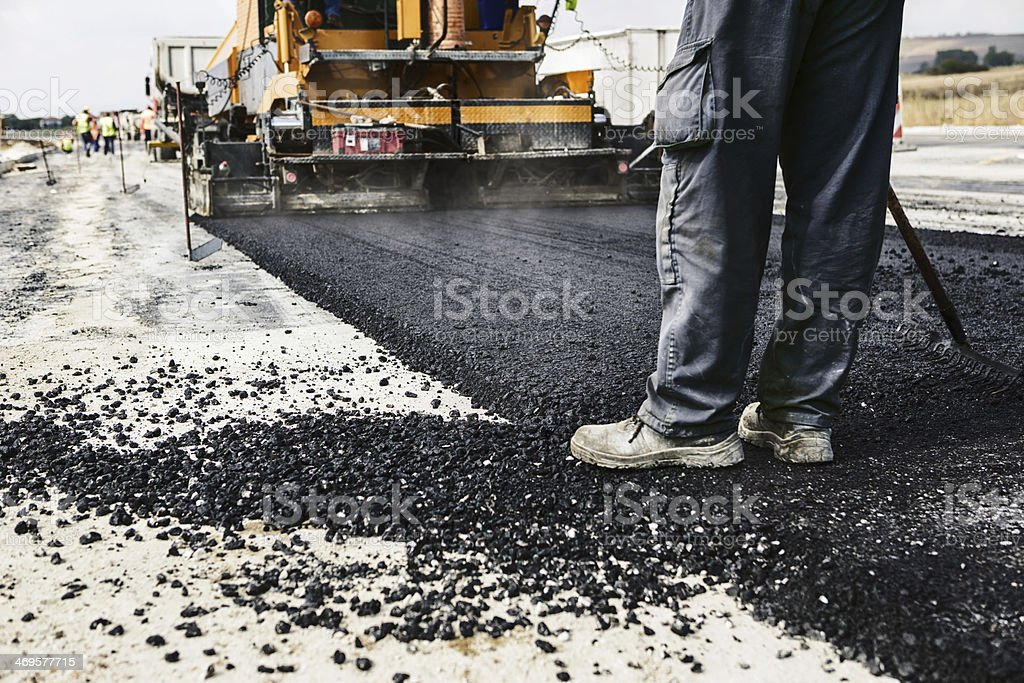 Man's legs on newly laid asphalt during road construction stock photo