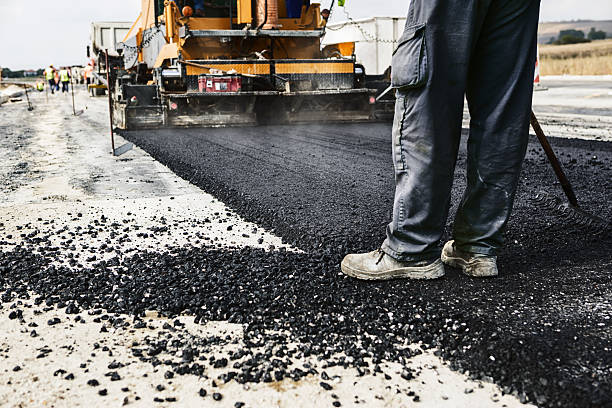 Man's legs on newly laid asphalt during road construction foto