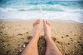 Man's legs on the beach