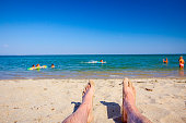 Man's legs are sunbathing by lying carefree on sand next to the coastline, on public beach.