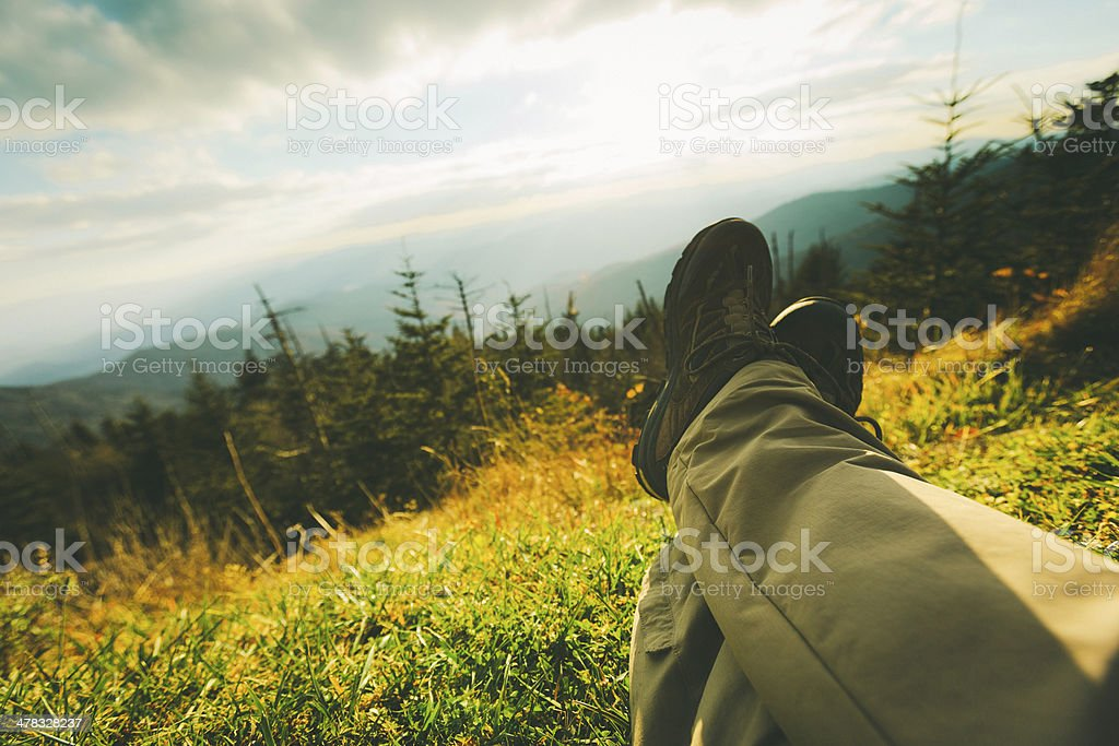 Man's Legs Relaxing in Mountain Landscape at Sunset royalty-free stock photo