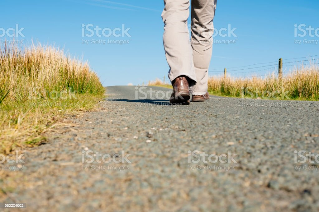 男人的腿行走在空的鄉村道路。 免版稅 stock photo