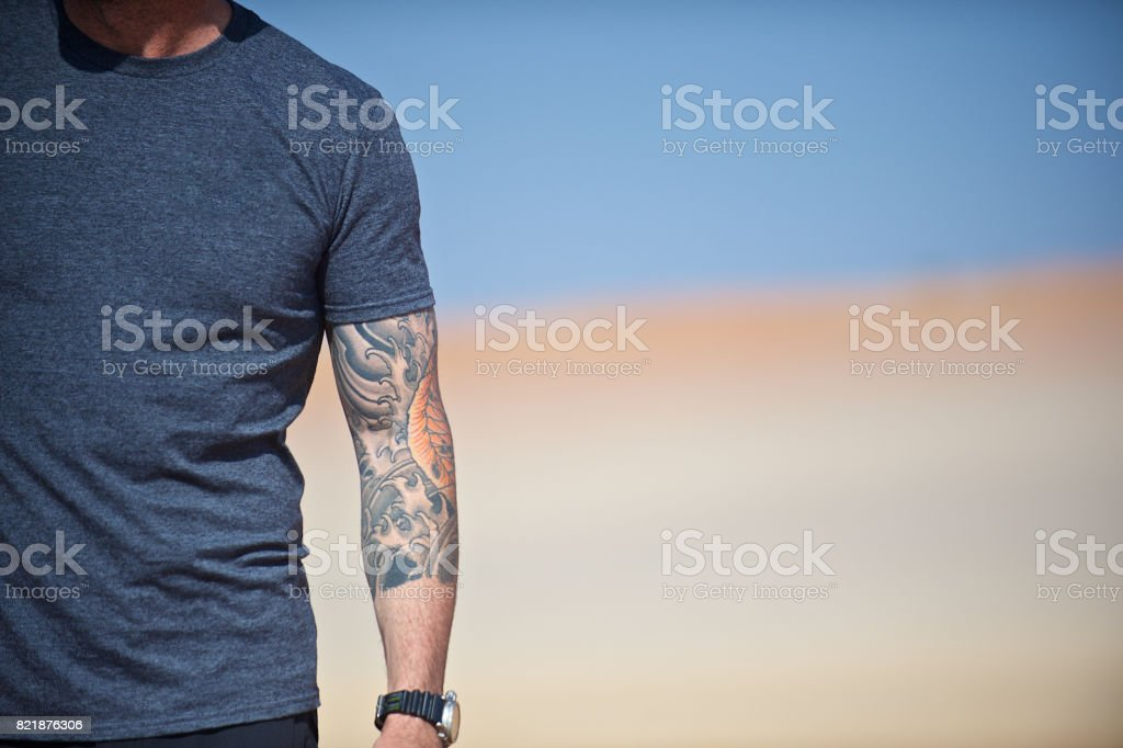 Man's mid body and arm with tattoos stock photo