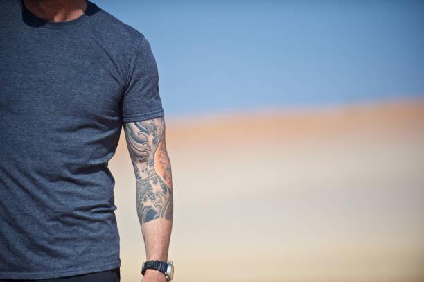 mannes mittleren körper und arm mit tattoos - namib wüste stock-fotos und bilder