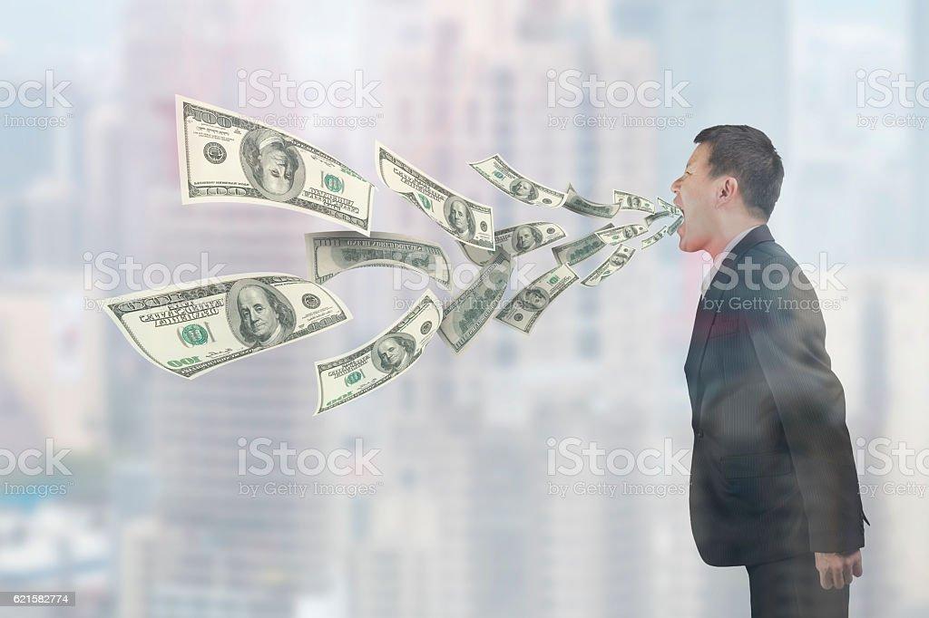 Man's mouth spraying out dollar bills stock photo