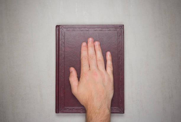 Palme de l'homme sur un livre, un serment sur la bible. Vue de dessus d'en haut - Photo