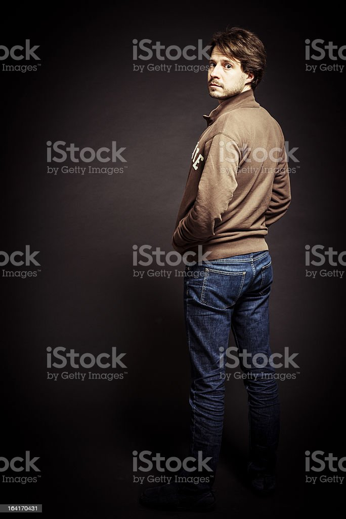 Man's portrait against brown wall in studio, rear view stock photo