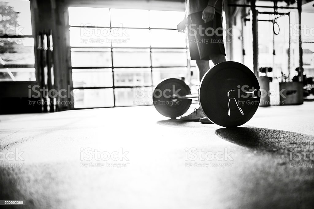 Mans Prepares to Lift Barbell in Gym stock photo
