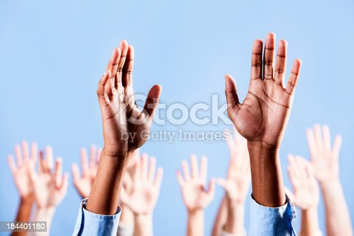 istock Man's raised hands with many more in background 184401180