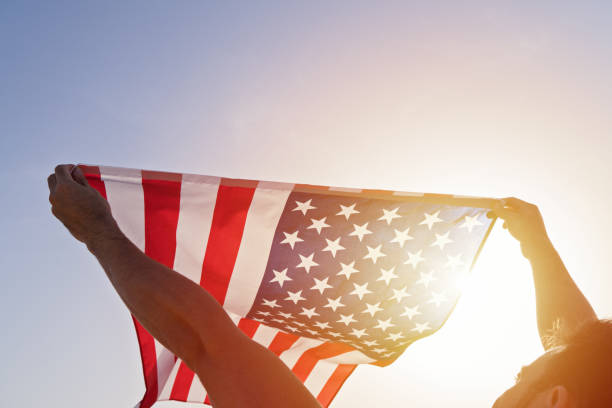 Man's raised hands with waving American Flag against clear blue sky stock photo