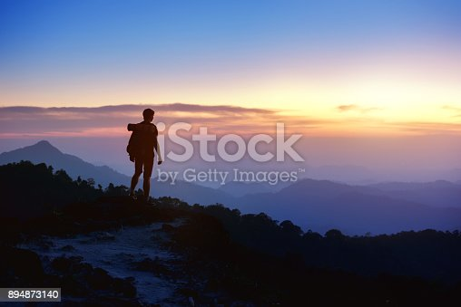 istock Man's silhouette on sunset mountains backdrop 894873140