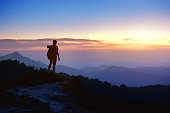 Silhouette of man with backpack at mountain top on background of sunset mountains