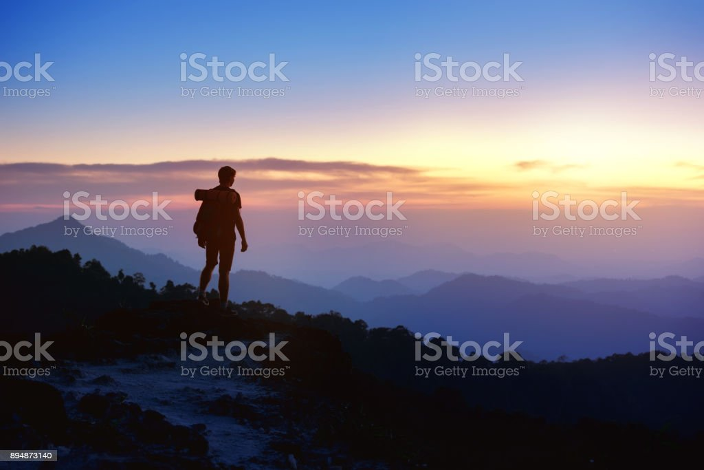 Man's silhouette on sunset mountains backdrop stock photo