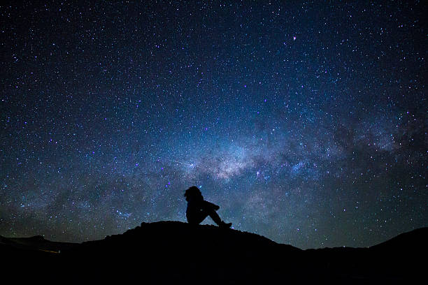 Man's silhouette sitted, staring at the milky way - Photo