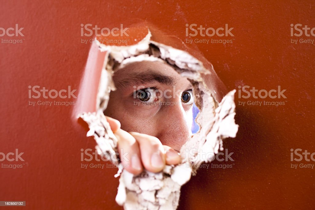 Man's spying through  hole in wall royalty-free stock photo