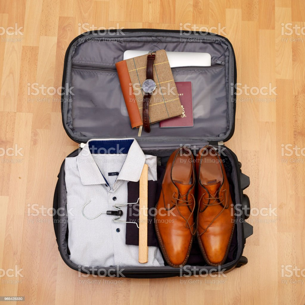 Man's suitcase for short vacation or citytrip on wooden floor royalty-free stock photo