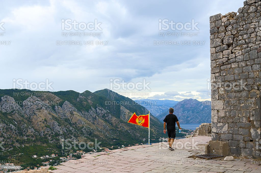 Man-tourist goes near ruins of ancient fortress above Bay of Kotor stock photo