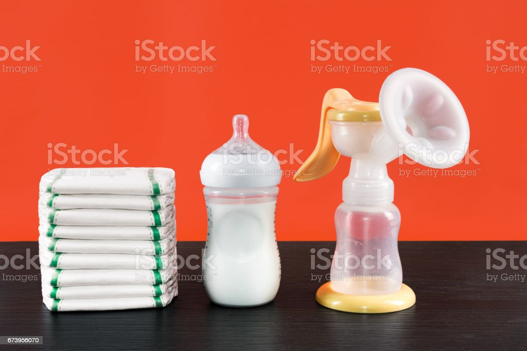 manual breast pump, baby bottle with milk. Mother care breast milk healthy food. Jar with milk in children's room breast feeding, bottle with breastmilk, diapers background - foto de acervo